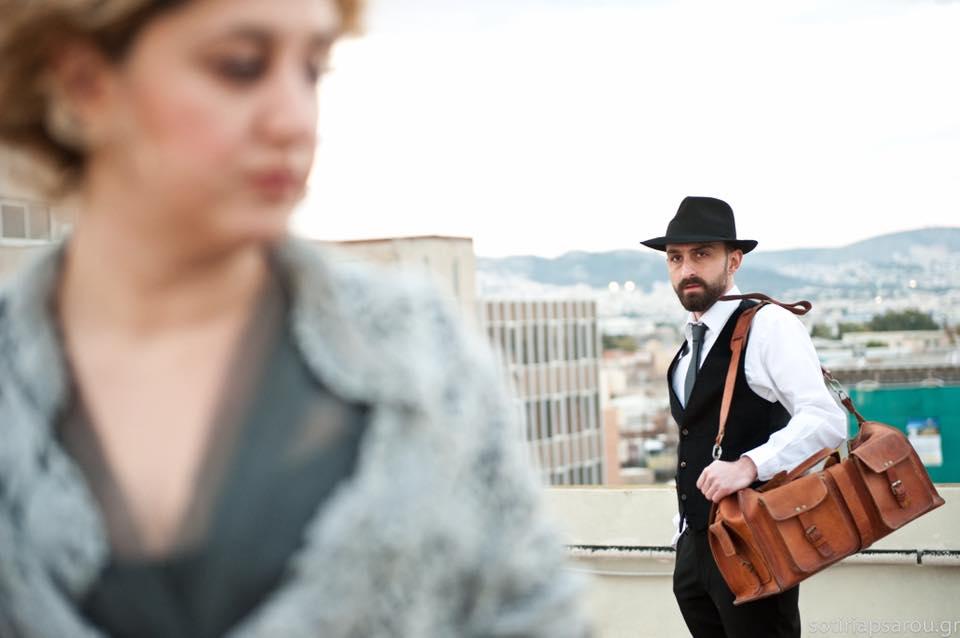 Φωτογραφία: Μία ηθοποιός με τα ξανθά μαλλιά της πιασμένα πάνω και ένα σάλι στους ώμους και ένας ηθοποιούς πίσω της με μαύρο παντελόνι, γιλέκο, γραβάτα και καπέλο και λευκό πουκάμισο να την κοιτά με μια καφέ ταξιδιωτική τσάντα στον ώμο. Κι εκείνη πάει να στραφεί προς εκείνον.